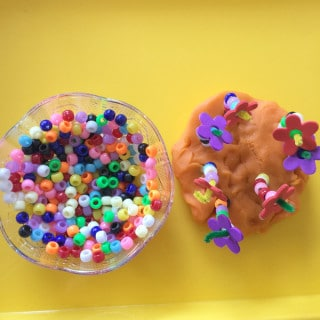 Spring play dough flower activity focuses on fine motor skills through the use of play dough